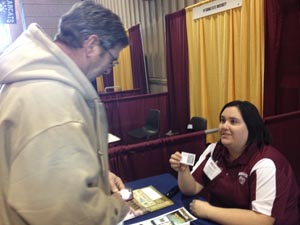 Katelyn McCoy shares information about Brownfield Mobile with a farmer at the Western Farm Show.