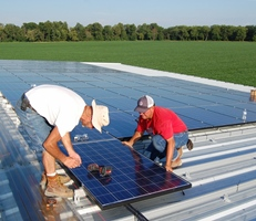 Stan Ruth, left, and Dennis Janowiak of Ecojiva install solar power system at Enterprise Hill Farm near Milan, Ohio